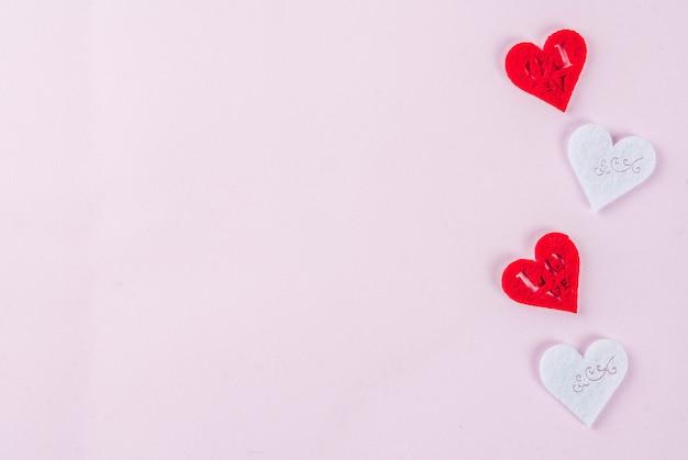 Día de san valentín rosa claro, tarjeta de felicitación, dos corazones rojos y dos corazones blancos decoración, vista superior copyspace