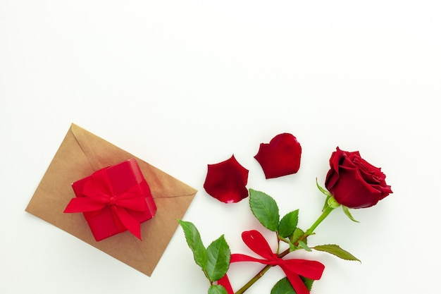 Día de san valentín. rosa roja con cinta, carta de amor y caja roja.