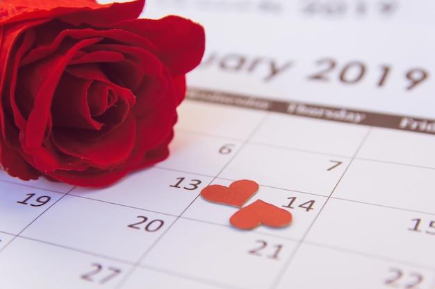 Día de san valentín. rosa roja y corazones rojos en la página de calendario 14 de febrero con copia espacio