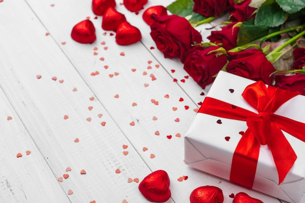Día de san valentín. rosas rojas y caja de regalo en mesa de madera
