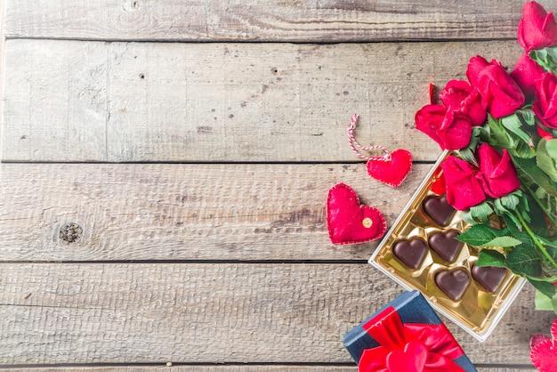 Día de san valentín con rosas rojas y corazón de chocolate.