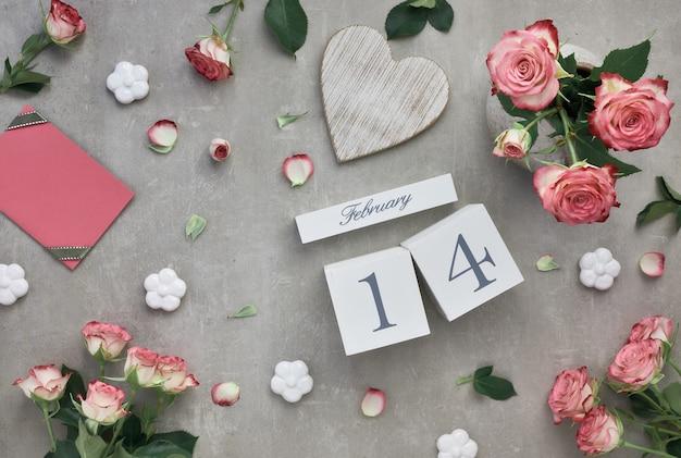 Día de san valentín con rosas rosadas y calendario de madera.