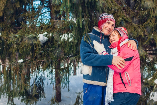 Día de san valentín. senior familia pareja abrazándose en bosque de invierno. feliz hombre y mujer caminando al aire libre.