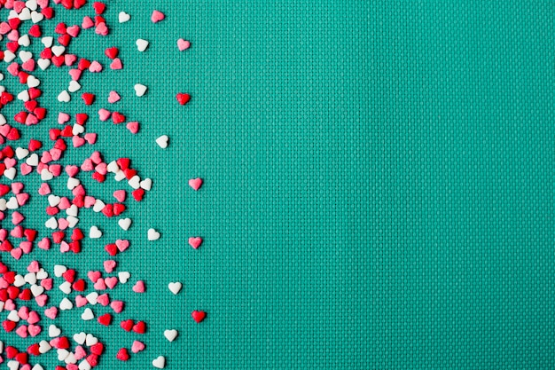 Día de san valentín sobre fondo verde con corazones rojos y blancos, vista superior