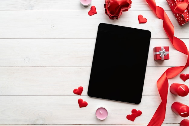 Día de san valentín. tableta con pantalla negra con decoraciones de san valentín velas, globos y confeti vista superior sobre fondo blanco de madera