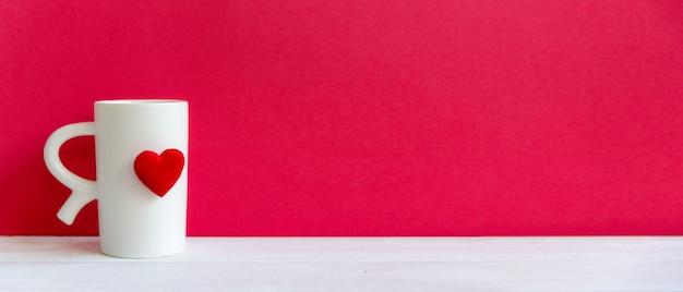 Día de san valentín con taza blanca café corazón rojo en la taza, fondo de pared roja, espacio de copia y banner para texto. concepto de san valentín