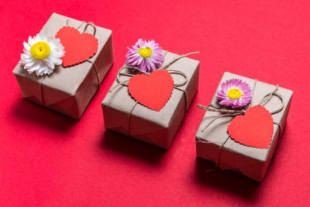 Día de san valentín tres cajas de regalo sobre fondo rojo.