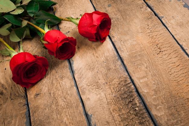 El día de san valentín tres rosas rojas en la mesa de madera antigua