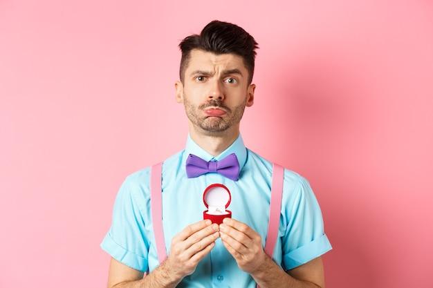 Día de san valentín. triste novio siendo rechazado, mostrando el anillo de compromiso y enfurruñada molesta, ella dijo que no, de pie sobre un fondo rosa.
