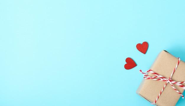 Día de san valentín, vista superior endecha plana, caja de regalo y corazón rojo sobre azul