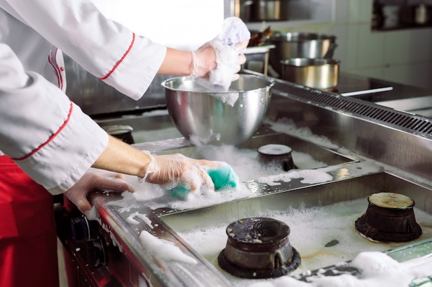 Día sanitario en el restaurante. los cocineros lavan horno, estufa y extractor en el restaurante.