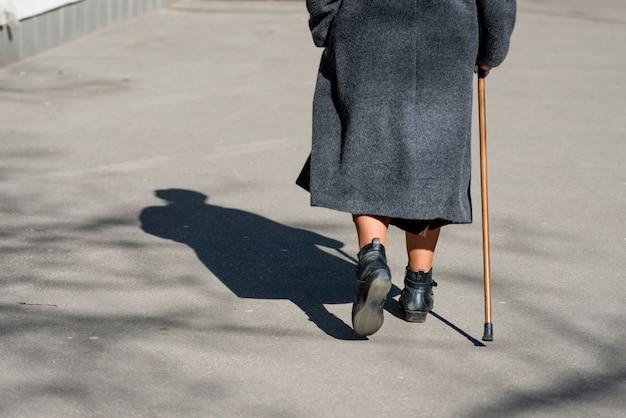 En un día soleado, una anciana caminando por la calle con un bastón.