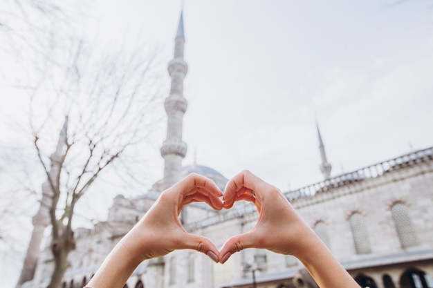 Día soleado con cielo azul. istanbul, turquía. sultan ahmet mosque en un día soleado. mujer hermosa que hace una forma del corazón con vistas a la mezquita de suleymaniye estambul.