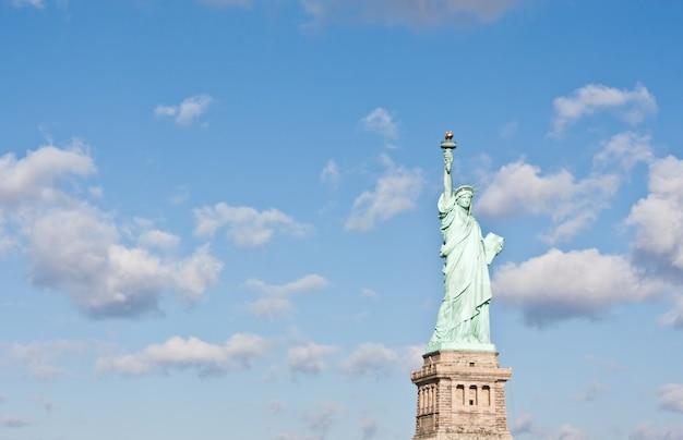 Día soleado, cielo azul con nubes: estatua de la libertad con espacio de copia