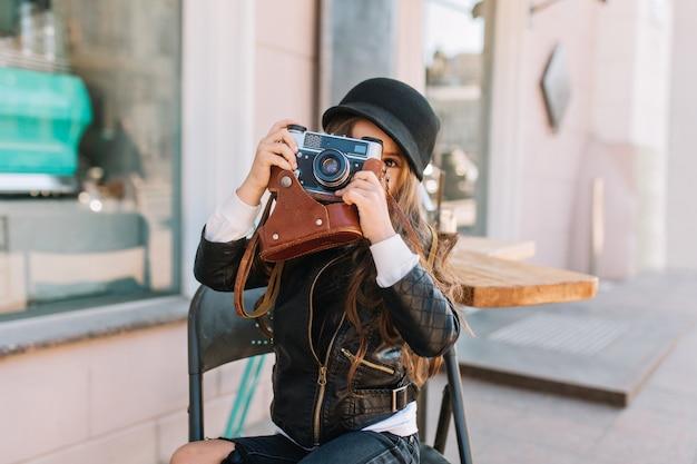 Día soleado de niña feliz que se sienta en la silla en el café de la ciudad y sonríe. ella está elegantemente vestida en su cámara retro de manos. le hace fotos a mamá, emociones verdaderas, buen humor ...