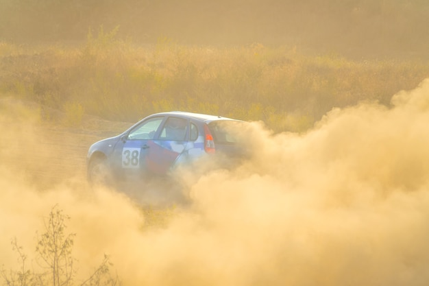 Día soleado de verano. el coche de color gira por el camino de tierra. mucho polvo