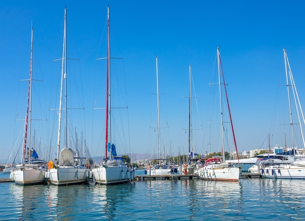 Día soleado de verano. pequeña ciudad griega. muchos yates de vela en un puerto deportivo.