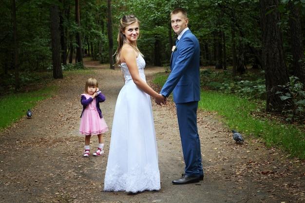 El día de su boda, los recién casados caminan en la tarde del bosque de verano con una niña de tres años.