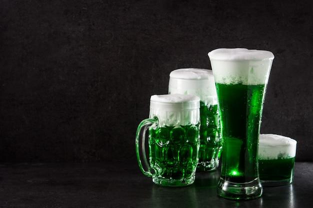 Día tradicional de san patricio cervezas verdes sobre fondo negro copia espacio