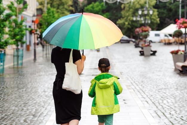 Día de verano con lluvia. familia feliz en un paseo durante la lluvia.