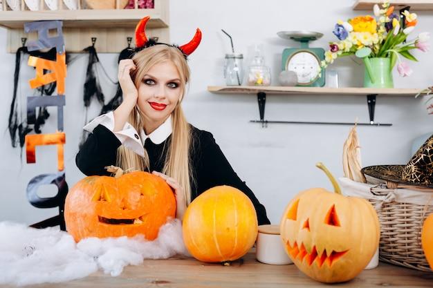 Diablo mujer sentada en la mesa junto a una calabaza de halloween
