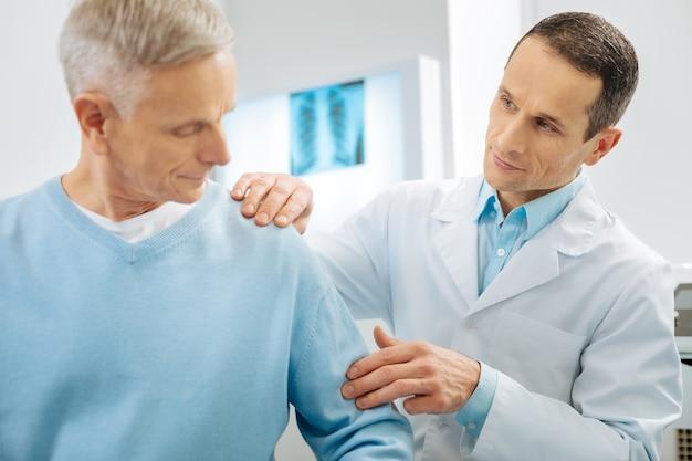 Diagnósticos médicos. doctor profesional agradable de pie cerca de su paciente y revisando su brazo mientras trabaja con él