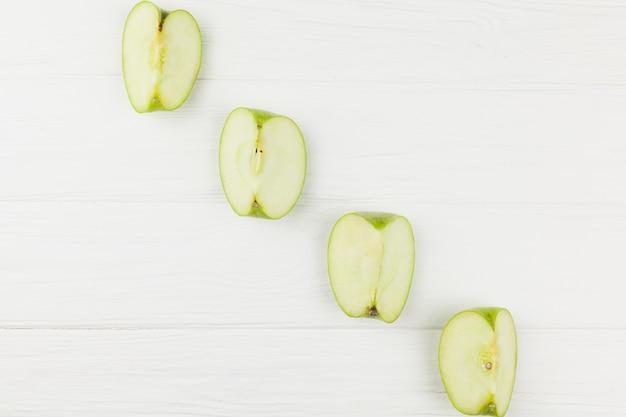 Diagonal de rodajas de manzanas sobre fondo blanco