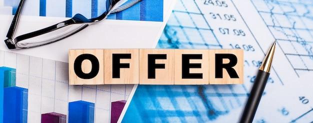 En los diagramas brillantes, vasos, un bolígrafo y cubos de madera con la palabra oferta. concepto de negocio