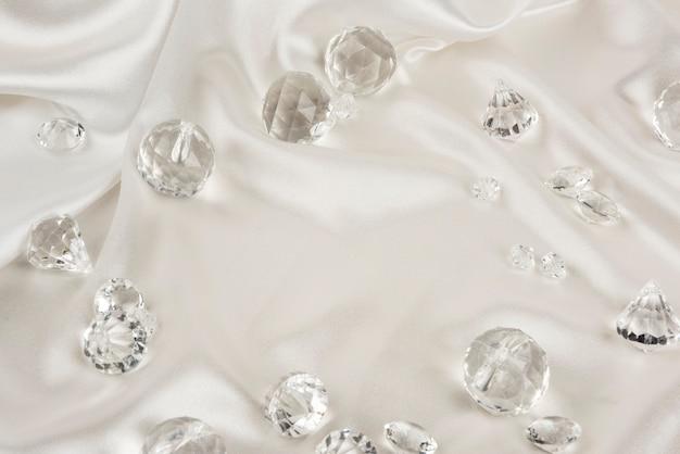 Diamantes transparentes decorativos sobre tela blanca con textura