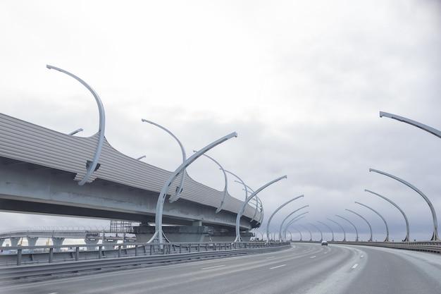 Diámetro occidental de alta velocidad en san petersburgo. cruce de transporte de la ciudad rotonda puesta de sol. línea de carretera. autopista de transporte moderna