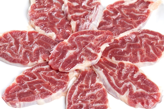 La diapositiva de carne cruda es la caña delantera aislada en un plato blanco.