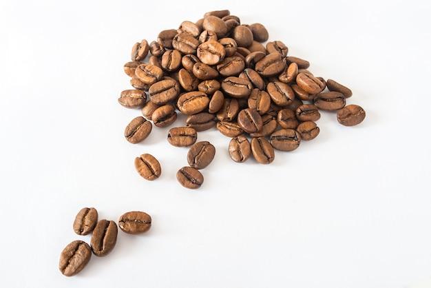 Diapositiva de granos de café sobre una superficie blanca