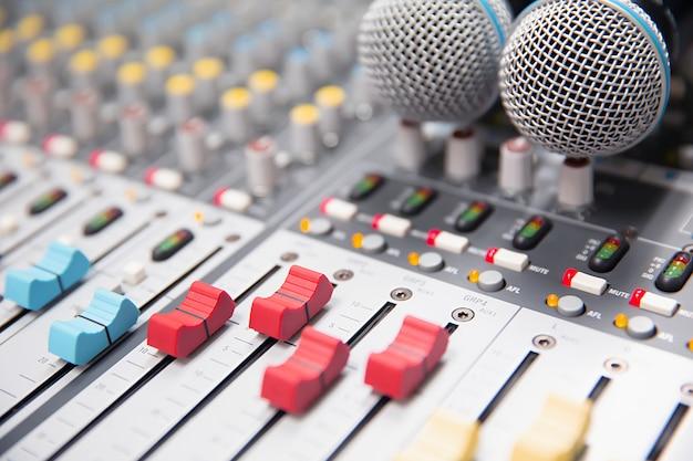 Diapositiva de volumen de primer plano del mezclador de sonido digital en el estudio.