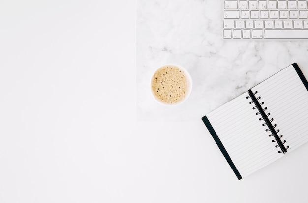 Un diario abierto; café y teclado en el escritorio con fondo blanco