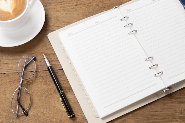 Diario abierto en la mesa de madera con bolígrafos y una taza de café con forma de corazón latte art