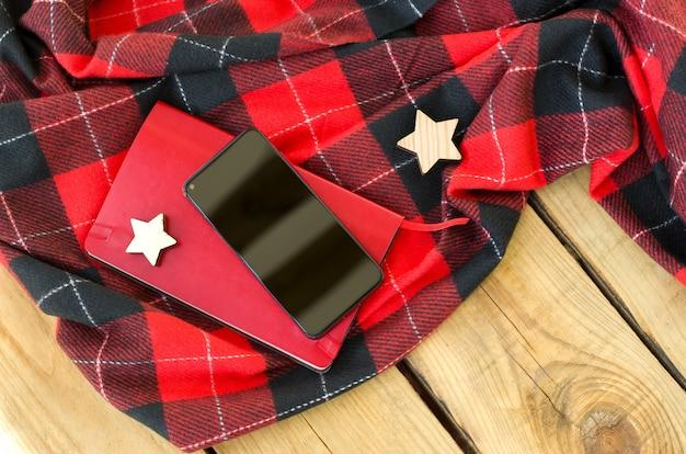Diario de billetera roja y teléfono inteligente sobre fondo de madera vista superior tiempo de compras en línea de navidad