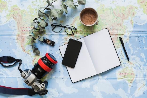 Diario en blanco, accesorios personales y taza de café en el mapa mundial
