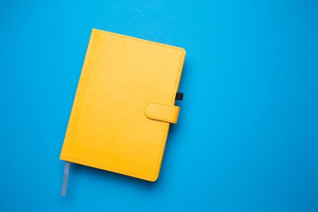 Diario de color amarillo en un primer plano de fondo azul aislado.