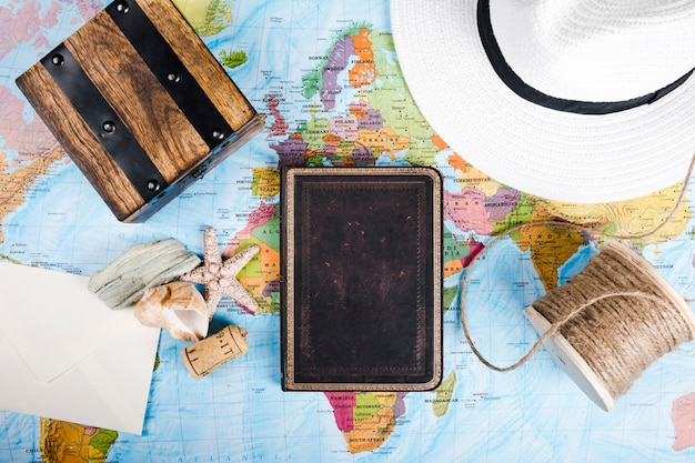 Diario, concha de mar, sombrero, caja de madera y carrete, en el mapa mundial