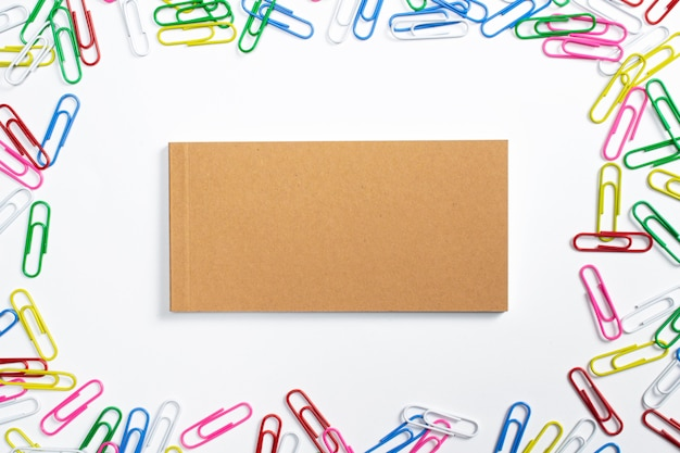 Diario de cuaderno en blanco con tapa dura de cartón en el centro y pernos de papel de colores alrededor aislado en blanco.