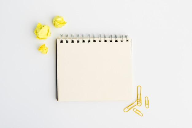 Diario espiral en blanco con papel arrugado amarillo y clip sobre fondo blanco.