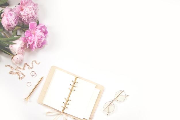 Diario femenino, bolígrafo dorado y joyas, peonías rosas sobre un fondo blanco. copia espacio