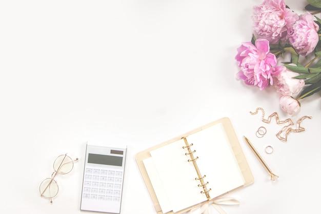 Diario femenino, pluma dorada y joyas, peonías rosas, calculadora sobre un fondo blanco. copia espacio