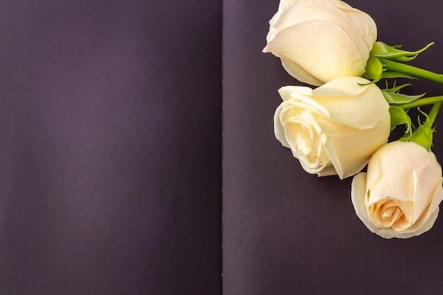 Diario negro abierto en blanco decorado con rosas blancas con espacio para texto o letras.