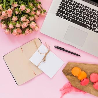 Diario de página en blanco; tarjeta; bolígrafo; ramo de flores; ordenador portátil; pluma y macarrones de tabla de cortar