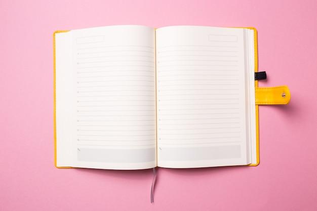 Diario con páginas en blanco abiertas para inscripción sobre un fondo rosa aislado.