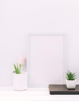 Diario; planta; flor de tulipán con marco de fotos en blanco en mesa blanca