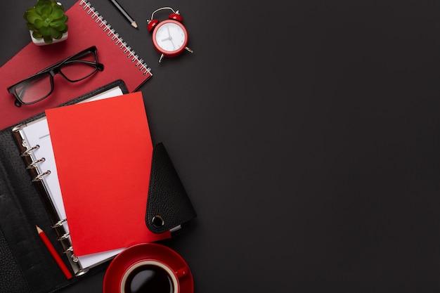 El diario rojo de la flor del despertador de la libreta de la taza de café del fondo anota el teclado en la tabla. vista superior con espacio de copia.