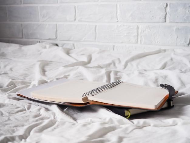 Diario sobre una tela blanca mentiras, el concepto de trabajo remoto, freelance, trabajo desde casa, comodidad, blogger