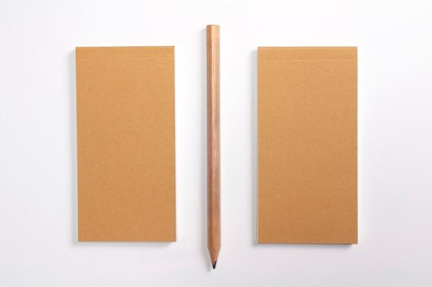 Diario con tapa dura de cartón en blanco y lápiz de madera aislado en blanco.